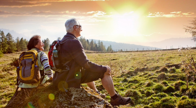Seniorpar på fjelltur i solnedgang